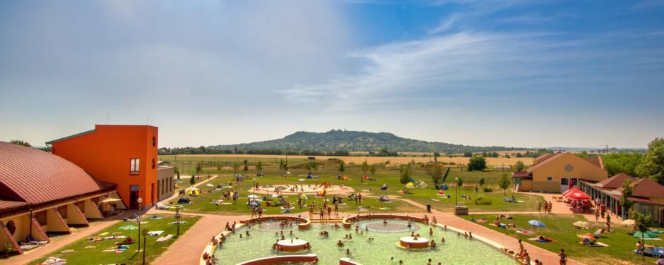 Sie sehen den Freiluftbereich der Vulkan Therme in Ungarn im Sommer. JUFA Hotels bietet erholsamen Thermen- und entspannten Wellnessurlaub für die ganze Familie.