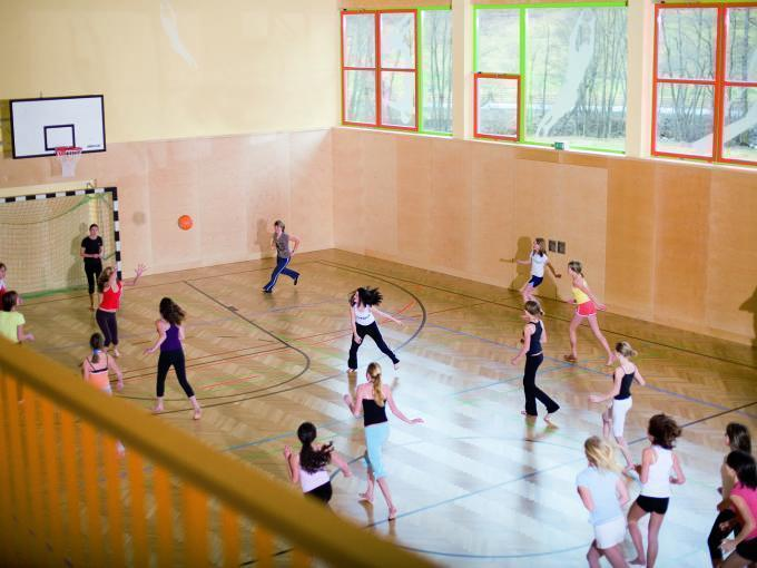 Sie sehen Kinder bei einem Ballsport in der Sporthalle der Sportarena. Die Zeit sportlich und mit viel Elan spielend gemeinsam verbringen im JUFA Hotel Wipptal. Der Ort für erholsamen Familienurlaub und einen unvergesslichen Winter- und Wanderurlaub.