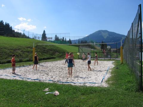 Teens spielen Volleyball am Beachvolleyballplatz beim JUFA Hotel Mariazell Erlaufsee Sport-Resort. Der Ort für erfolgreiches Training in ungezwungener Atmosphäre für Vereine und Teams.