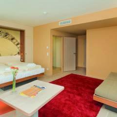 Bett in Suite im JUFA Hotel Wien City mit Sofa. Der Ort für erlebnisreichen Städtetrip für die ganze Familie und der ideale Platz für Ihr Seminar.