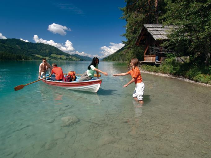 Menschen auf einer Bootsfahrt am Weissensee in Kärnten im Sommer. JUFA Hotels bietet tollen Sommerurlaub an schönen Seen für die ganze Familie.