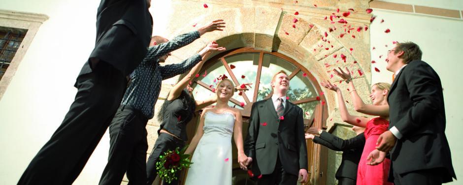 Brautpaar wird bei Hochzeit von Gästen mit Blüten überworfen. JUFA Hotels bietet Ihnen den idealen Ort für märchenhafte Hochzeiten.