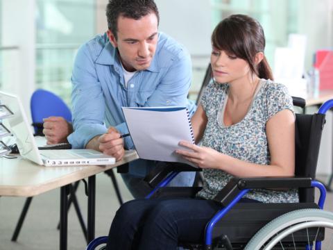 Bürobesprechnung mit Frau im Rollstuhl und Mann. JUFA Hotels bietet eine tolle Arbeitsatmoshäre und viele Aufstiegsmöglichkeiten.