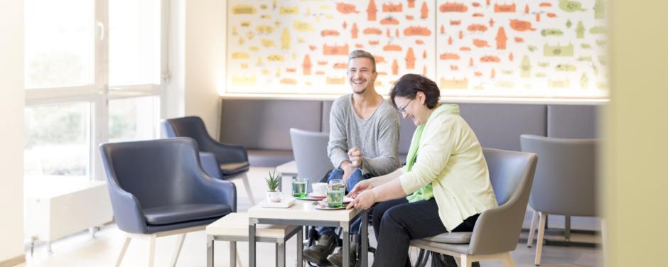 Cafe und Lobby barrierefrei mit Menschen im JUFA Hotel Graz City. Der Ort für erlebnisreichen Städtetrip für die ganze Familie und der ideale Platz für Ihr Seminar.