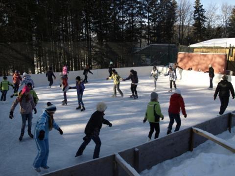 Kinder und Erwachsene beim Eislaufen auf dem Mariazeller Eislaufplatz im JUFA Hotel Urlaub. Der Ort für erholsamen Familienurlaub und einen unvergesslichen Winterurlaub