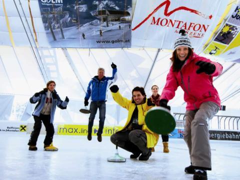 Junge Menschen beim Eisstockschießen auf der Kunsteisbahn im Aktivpark in Montafon. Der Ort für erholsamen Familienurlaub und einen unvergesslichen Winterurlaub.