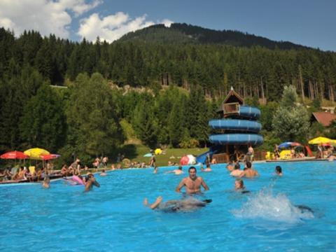 Menschen baden im Erlebnisschwimmbad in Gitschtal im Sommer in der Nähe von JUFA Hotels. Der Ort für erholsamen Familienurlaub und einen unvergesslichen Winter- und Wanderurlaub.
