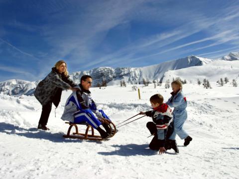 Familie mit Kindern beim Rodelfahren in der Urlaubsregion Pyhrn-Priel