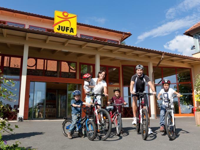 Familie mit Rädern vorm Eingang des JUFA Hotel Deutschlandsberg - Sport-Resort. Der Ort für erfolgreiches Training in ungezwungener Atmosphäre für Vereine und Teams.