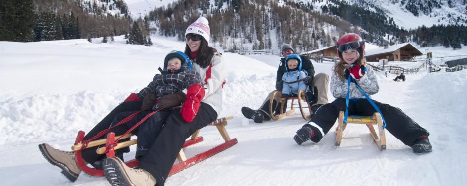 Familien beim Rodeln im JUFA Hotel Wipptal Urlaub. Der Ort für erholsamen Familienurlaub und einen unvergesslichen Winterurlaub.