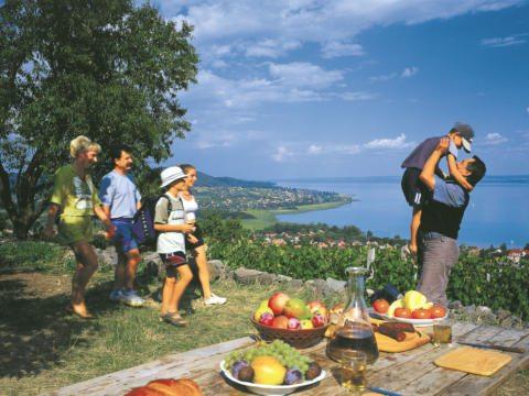 Familie beim Picknick mit fantastischem Blick auf den Plattensee im Sommer. JUFA Hotels bietet erholsamen Thermen- und entspannten Wellnessurlaub für die ganze Familie.
