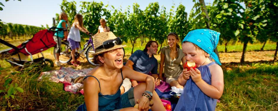 Familie hat Spass beim Picknick in der Natur und Kind beisst in Apfel im Burgenland. JUFA Hotels bietet erholsamen Familienurlaub und einen unvergesslichen Winter- und Wanderurlaub.
