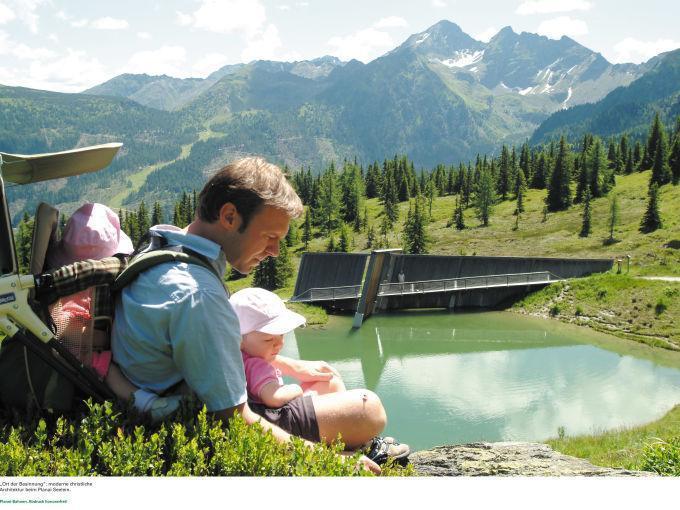 Vater wandert mit Kindern in der Region Schladming-Dachstein neben einem Bergsee. JUFA Hotels bietet erholsamen Familienurlaub und einen unvergesslichen Winter- und Wanderurlaub.