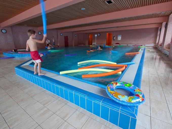 Menschen baden im Schwimmbecken im Hallenbad im JUFA Hotel Mariazell Sigmundsberg. Der Ort für erholsamen Familienurlaub und einen unvergesslichen Winter- und Wanderurlaub.