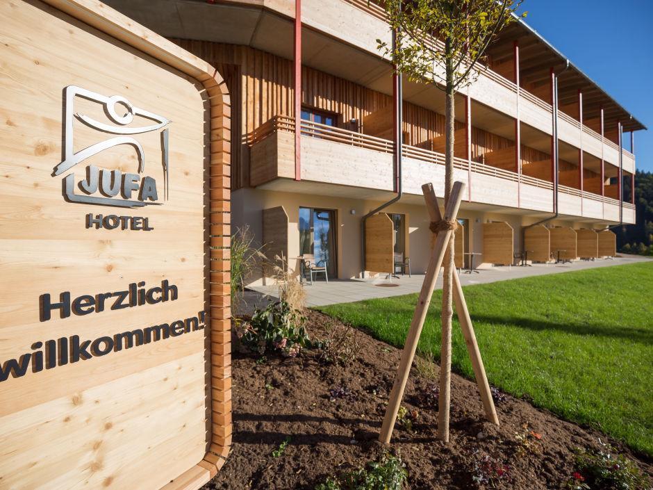 Aussenansicht vom JUFA Hotel Annaberg - Bergerlebnis-Resort mit Willkommensschild im Sommer. Der Ort für erholsamen Familienurlaub und einen unvergesslichen Winter- und Wanderurlaub.