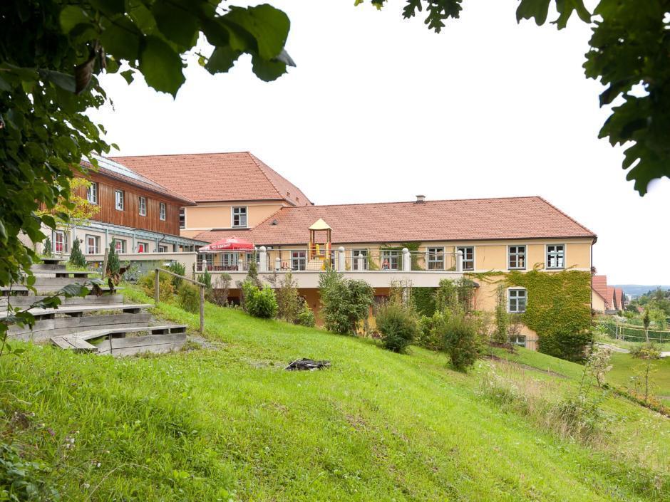 Aussenansicht mit Garten vom JUFA Hotel Deutschlandsberg - Sport-Resort. Der Ort für erfolgreiches Training in ungezwungener Atmosphäre für Vereine und Teams.