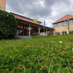 Aussenansicht mit Wiese vom JUFA Hotel Deutschlandsberg - Sport-Resort.Der Ort für erfolgreiches Training in ungezwungener Atmosphäre für Vereine und Teams.