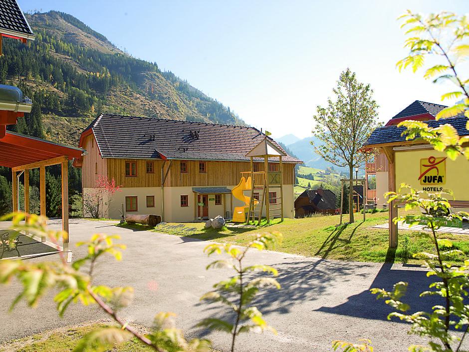 Aussenansicht vom JUFA Hotel Donnersbachwald - Almerlebnis im Sommer. Der Ort für erholsamen Familienurlaub und einen unvergesslichen Winter- und Wanderurlaub.