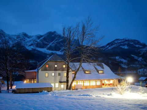 Aussenansicht vom JUFA Hotel Grundlsee mit winterlicher Abendstimmung. Der Ort für tollen Urlaub an schönen Seen für die ganze Familie.