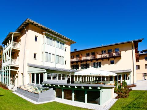 Aussenansicht mit Sonnenterrasse im Sommer vom JUFA Hotel Kaprun. Der Ort für erholsamen Familienurlaub und einen unvergesslichen Winter- und Wanderurlaub.