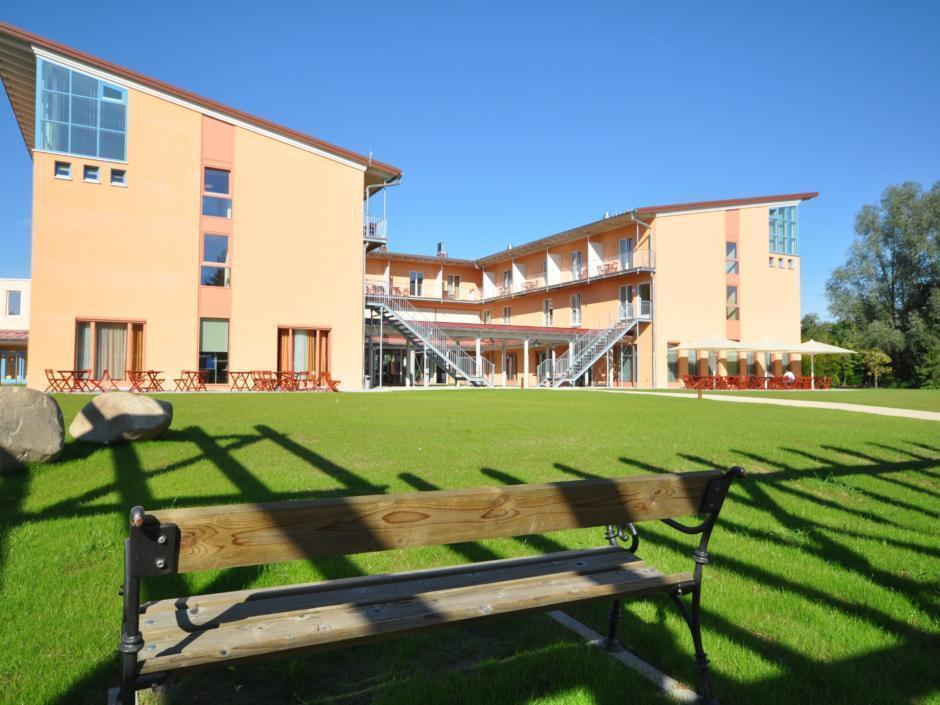 Hotelansicht mit Parkbank und Garten im Sommer vom JUFA Kempten Familien-Resort. Der Ort für kinderfreundlichen und erlebnisreichen Urlaub für die ganze Familie.