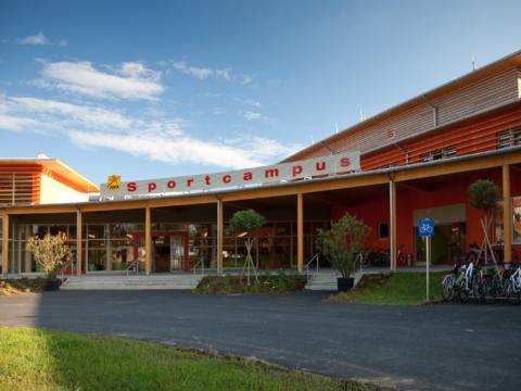 Aussenansicht mit Eingang im Sommer vom JUFA Hotel Leibnitz - Sport-Resort. Der Ort für erfolgreiches Training in ungezwungener Atmosphäre für Vereine und Teams.