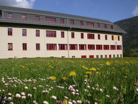 Aussenansicht mit Blumenwiese im Sommer vom JUFA Hotel Lungau. Der Ort für erholsamen Familienurlaub und einen unvergesslichen Winter- und Wanderurlaub.