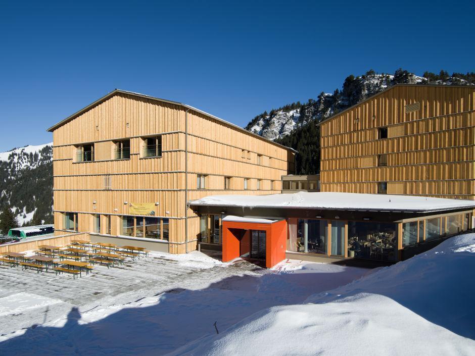 Aussenansicht mit Terrasse im Winter vom JUFA Hotel Malbun Alpin-Resort. Der Ort für erholsamen Familienurlaub und einen unvergesslichen Winter- und Wanderurlaub.