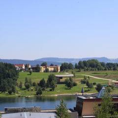 Aussenansicht von der Ferne mit See vom JUFA Hotel Maria Lankowitz. Der Ort für tollen Sommerurlaub an schönen Seen für die ganze Familie.