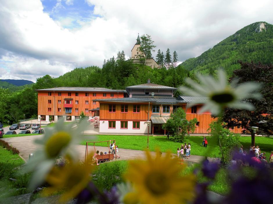 Aussenansicht mit Blumen im Sommer vom JUFA Hotel Mariazell Sigmundsberg. Der Ort für erholsamen Familienurlaub und einen unvergesslichen Winter- und Wanderurlaub.