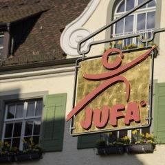Aussenansicht mit Schild vom JUFA Hotel Meersburg. Der Ort für tollen Sommerurlaub an schönen Seen für die ganze Familie.