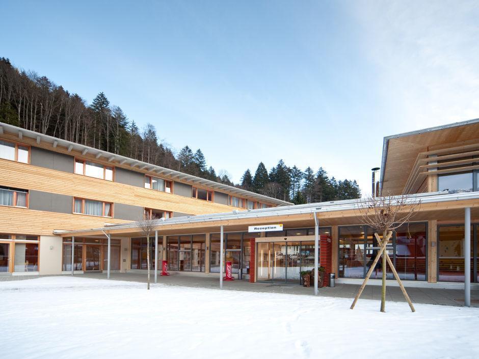 Aussenansicht mit Eingang im Winter vom JUFA Hotel Montafon. Der Ort für erholsamen Familienurlaub und einen unvergesslichen Winter- und Wanderurlaub.