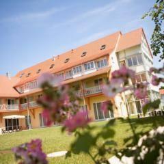 Aussenansicht mit Blumen im Sommer vom JUFA Hotel Nördlingen. Der Ort für kinderfreundlichen und erlebnisreichen Urlaub für die ganze Familie.