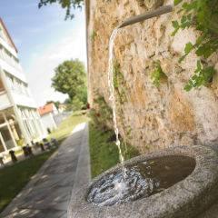 Aussenansicht mit Brunnen und Garten im Sommer vom JUFA Hotel Nördlingen. Der Ort für kinderfreundlichen und erlebnisreichen Urlaub für die ganze Familie.