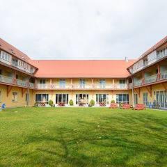 Aussenansicht mit Terrasse und Garten im Sommer vom JUFA Hotel Nördlingen. Der Ort für kinderfreundlichen und erlebnisreichen Urlaub für die ganze Familie.
