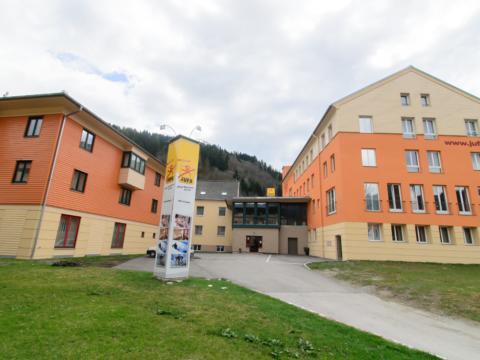 Aussenansicht mit Wiese im Sommer vom JUFA Hotel Schladming. Der Ort für erholsamen Familienurlaub und einen unvergesslichen Winter- und Wanderurlaub.