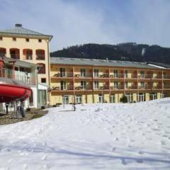 Aussenansicht mit Aussenrutsche im Winter vom JUFA Hotel Veitsch. Der Ort für kinderfreundlichen und erlebnisreichen Urlaub für die ganze Familie.