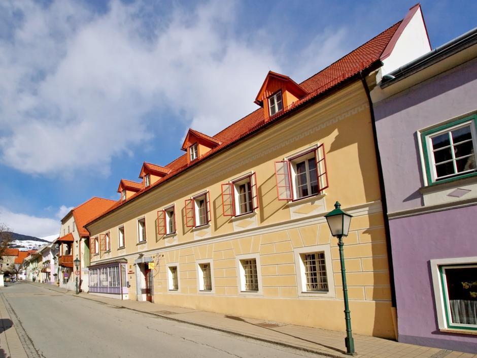 Aussenansicht mit Strasse im Sommer vom JUFA Hotel Oberwölz. Der Ort für erholsamen Familienurlaub und einen unvergesslichen Winter- und Wanderurlaub.
