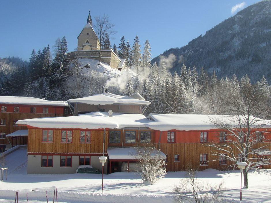 Aussenansicht vom JUFA Hotel Mariazell Sigmundsberg mit Hauskapelle im Winter. Der Ort für erholsamen Familienurlaub und einen unvergesslichen Winter- und Wanderurlaub.