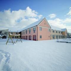 Hotelansicht im Winter mit Schaukel vom JUFA Hotel Pöllau - Bio-Landerlebnis. Der Ort für erlebnisreichen Natururlaub für die ganze Familie.