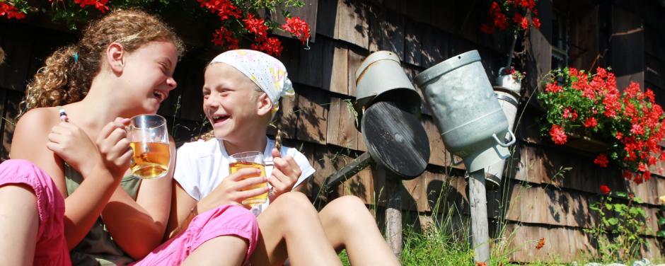 Kinder trinken ein Glas Apfelsaft in einer Wiese vor einer Almhütte im Sommer. JUFA Hotels bietet Ihnen den Ort für erlebnisreichen Natururlaub für die ganze Familie.