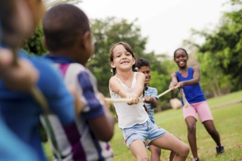 Kinder beim Tauziehen auf der Wiese. JUFA Hotels bietet erlebnisreiche Feriencamps in den Bereichen Sport, Gesundheit, Bildung und Sprachen.