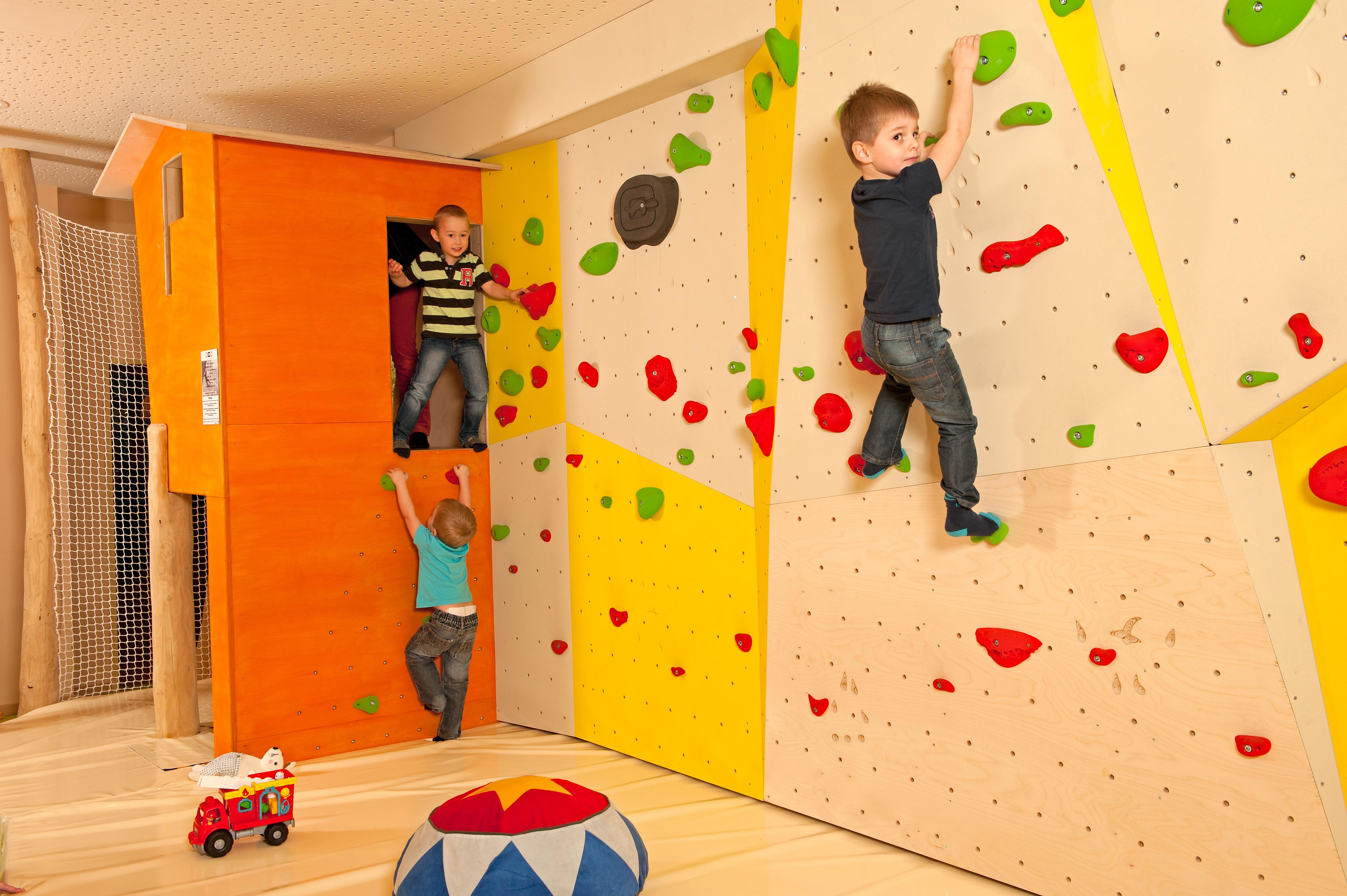 Kind klettert an der Kletterwand im Spielbereich des JUFA Hotel Almtal. Der Ort für erholsamen Familienurlaub und einen unvergesslichen Winter- und Wanderurlaub.
