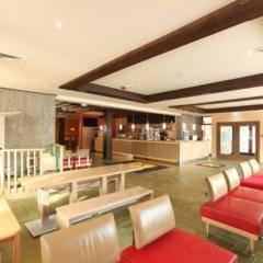 Lobby mit Rezeption und Spielbereich im JUFA Hotel Altenmarkt. Der Ort für erholsamen Familienurlaub und einen unvergesslichen Winterurlaub.