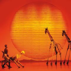 Tanzende Menschen auf der Bühne des Musicals der König der Löwen in Hamburg. Der Ort für erholsamen Familienurlaub.