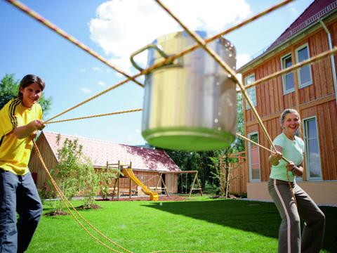 Paar versucht sich beim Kooperationsspiel im Garten im Sommer. JUFA Hotels bietet starkes und kreatives Teambuildung in abwechslungsreichen Regionen.