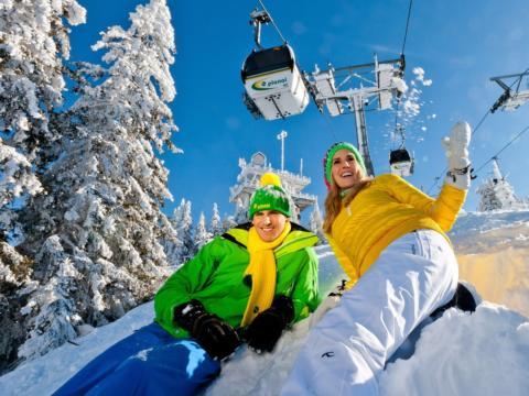 Paar liegt im Schnee auf der Planai bei Sonnenschein und mit Gondel im Hintergrund.  JUFA Hotels bietet erholsamen Familienurlaub und einen unvergesslichen Winterurlaub.