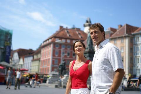 Paar steht am Hauptplatz in graz und geniesst den Städtetrip. JUFA Hotels bietet erlebnisreichen Städtetrip für die ganze Familie und den idealen Platz für Ihr Seminar.