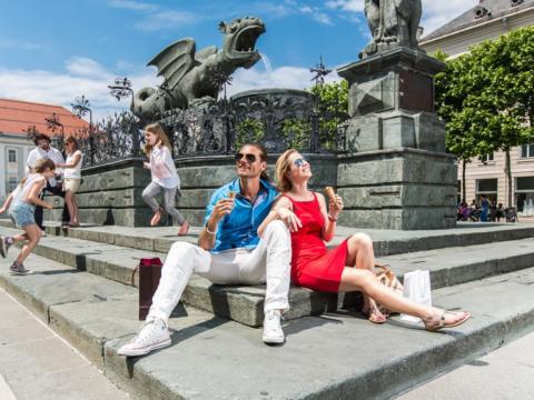 Paar beim Eisessen vor dem Lindwurm in Klagenfurt im Sommer, dahinter hüpfen Kinder über die Treppen am Brunnen. JUFA Hotels bieten erholsamen Familienurlaub und einen unvergesslichen Winter- und Wanderurlaub.