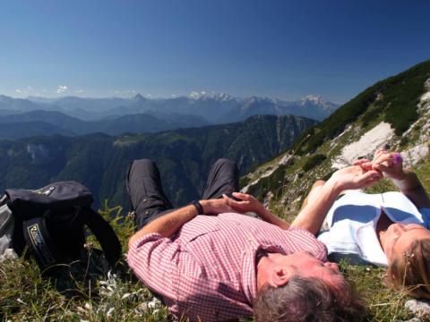 Paar ruht sich beim Wandern in der Wiese aus in Niederösterreich mit Bergblick. JUFA Hotels bietet erholsamen Familienurlaub und einen unvergesslichen Winter- und Wanderurlaub.